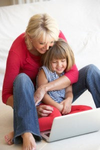 Middle age woman with young girl using laptop computer
